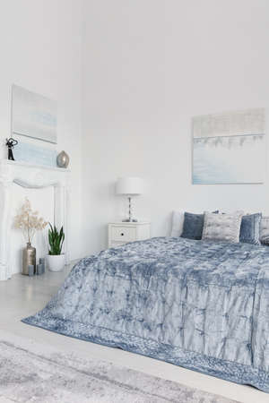 Plants and lamp next to blue bed in white minimal bedroom interior with posters. Real photo Stockfoto