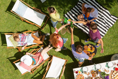 High angle on friends on sunbeds making toast with bottles during party in the garden Stock Photo