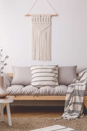 White handmade macrame above comfortable beige living room sofa with lot of pillows and blanket with stripes Stock Photo