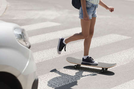 Girl on skateboard on pedestrian crossing Stock Photo