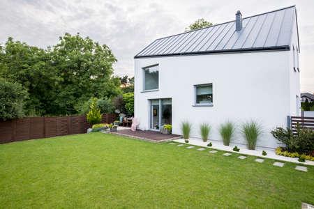 Grünes Gras und Bäume vor weißem Haus mit Fenstern und grauem Dach. Echtes Foto Standard-Bild