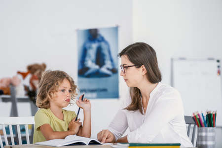 A young female tutor having a lesson with an absentminded child with concentration issues.