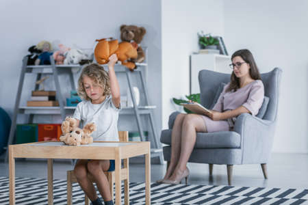 A child with behavioral problems sitting by a table and hitting a teddy bear during a therapeutic meeting with a therapist in a family support center.