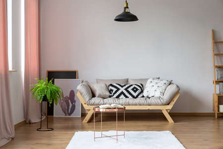 Copy space on the empty white wall in eclectic loft interior with beige scandinavian sofa and plant in pot