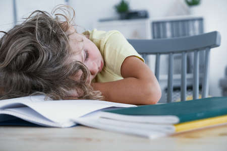 Close-up of a tired kid sleeping with his head rested on a table with a book. Stock Photo