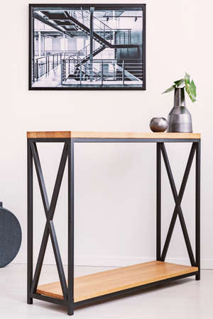 Vase with leaf and candle standing on stylish modern table with metal legs. Industrial poster on the wall above it Stockfoto
