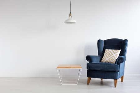 Biała prosta lampa nad drewnianym stolikiem kawowym w stylowym minimalistycznym wnętrzu z ciemnoniebieskim fotelem z wzorzystą poduszką, prawdziwe zdjęcie z miejscem na kopię Zdjęcie Seryjne