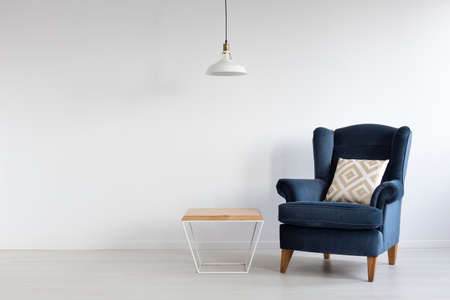 White simple lamp above wooden coffee table in stylish minimal interior with dark blue armchair with patterned pillow, real photo with copy space
