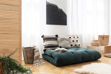 Fur and basket next to green futon with pillows in boho bedroom interior with poster. Real photo