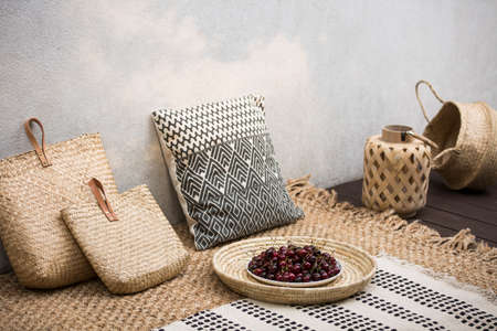 Rattan bags next to patterned pillow on carpet in bright dining room interior with plate. Real photo