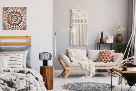 Interior plano pequeño espacio abierto con sofá beige con cojín, macramé en la pared, perchero con velas y plantas y cama con almohadas