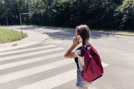 Teenager girl with backpack going to school and talking on the phone