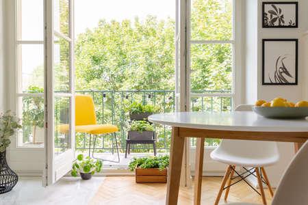 Gelber Stuhl auf dem Balkon des eleganten Kücheninnenraums mit weißem Holzstuhl und Postern an der Wand, echtes Foto
