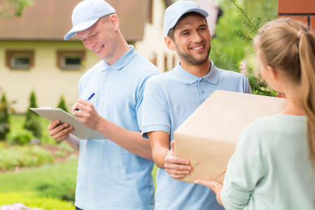 Smiling couriers in blue uniforms and caps giving package to a customer Stock Photo