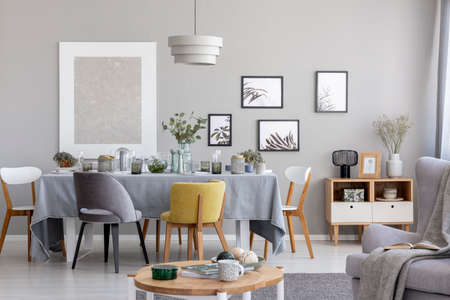 Chairs at table with grey cloth in modern dining room interior with posters and lamp. Real photo Stock Photo