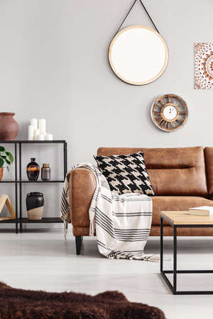 Vertical view of warm ethno living room with leather couch with patterned pillow and mirror and clock on beige wall, real photo