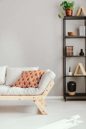 Patterned pillow on scandinavian sofa next to shelf with different kind of accessories, real photo with copy space Stock Photo