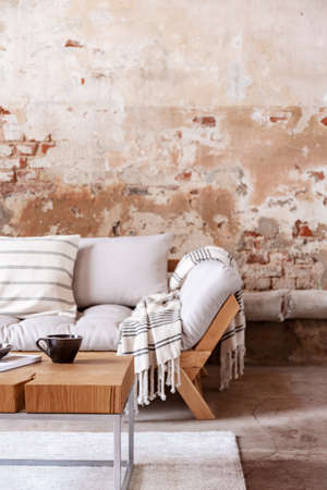 Blanket on wooden sofa in minimal loft interior with table and red brick wall. Real photo Stock Photo