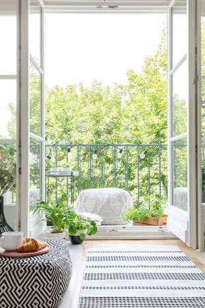Vista vertical de la habitación con la puerta del balcón abierta, foto real