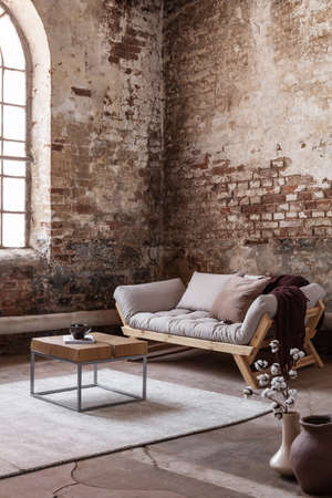 Wooden table on carpet in front of settee in loft interior with flowers and red brick wall. Real photo