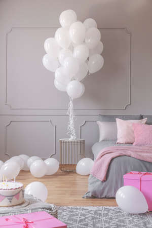 Birthday bedroom design with white balloons and cake with candles and presents, real photo