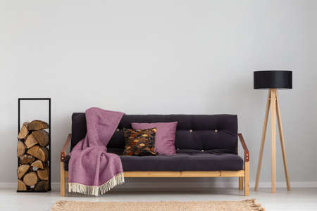 Log of wood next to comfortable sofa with dark lilac blanket and pillows, stylish wooden lamp with black lampshade, real photo copy space on the empty grey wall