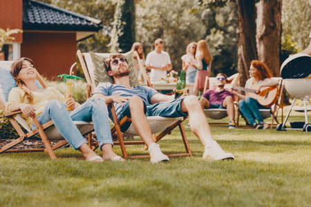 Smiling friends relaxing on sunbeds during outdoor party in the garden Stock Photo