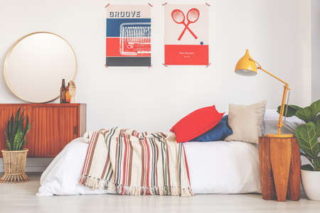 Posters above bed with striped blanket in bedroom interior with plant and yellow lamp. Real photo
