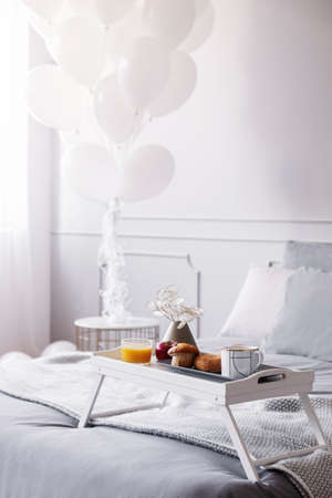 Wooden tray with breakfast and flowers on cozy bed, birthday bedroom design concept