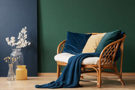 Glass vases with flowers next to comfortable rattan settee with blue, emerald and beige pillows and blanket, real photo with copy space on empty green wall