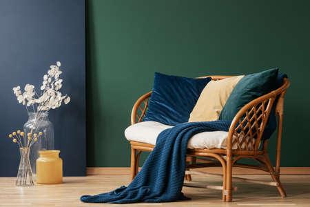 Glasvasen mit Blumen neben einem bequemen Rattansofa mit blauen, smaragdgrünen und beige Kissen und Decke, echtes Foto mit Kopienraum auf leerer grüner Wand