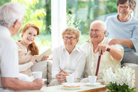 Smiling senior people drinking tea with caregiver in the common room of nursing house