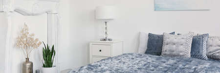 Panorama of plants and lamp on cabinet in white bedroom interior with cushions on blue bed. Real photo