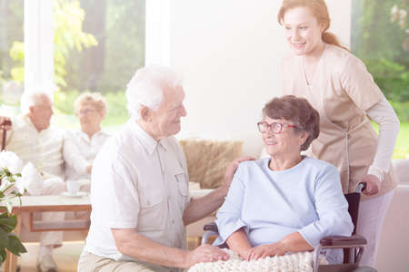 Smiling elderly man visiting happy senior woman in the wheelchair supported by nurse