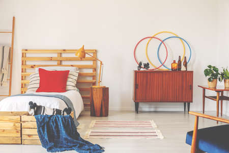 Wooden cabinet next to bed with red cushion and blue blanket in retro bedroom interior. Real photo