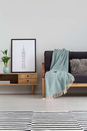 Vertical view of sofa with pastel blue blanket next to wooden cabinet with poster in back frame, real photo with copy space on the wall