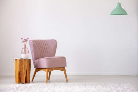 Flowers on wooden stool next to pink armchair in flat interior with copy space and mint lamp. Real photo