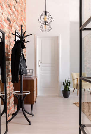 Vertical view of elegant entrance hall with white door and wooden furniture in stylish apartment with brick wall, real photo