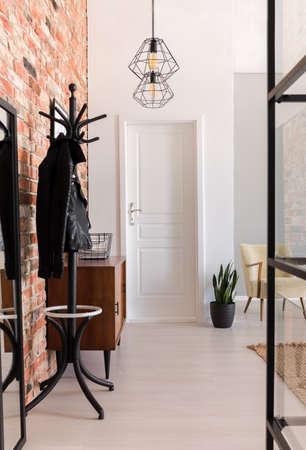 Verticale weergave van elegante inkomhal met witte deur en houten meubilair in stijlvol appartement met bakstenen muur, echte foto Stockfoto