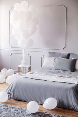 White balloons in stylish grey bedroom with comfortable king size bed with grey bedding and blanket, real photo with copy space on the empty wall Stock Photo