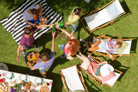 Top view on group of friends making toast and relaxing on sunbeds during garden party Stock Photo