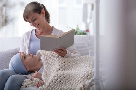 Smiling mother reading book to sick child with cancer wearing headscarf