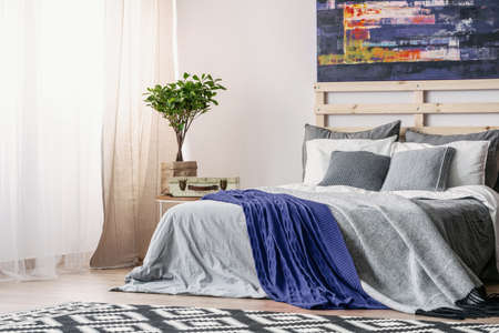 Abstract painting above king size bed with grey bedding and blue cozy blanket in scandinavian bedroom interior, real photo with copy space