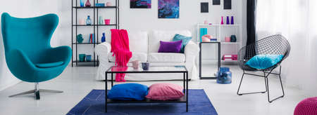 Table on blue carpet in white living room interior with armchair and pink blanket on sofa. Real photo Stockfoto