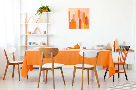 Wooden chairs at orange table in white dining room interior with poster and plant. Real photo Stock Photo