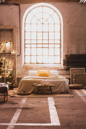 Cushions on bed in spacious industrial bedroom interior with window and wooden bench on carpet. Real photo
