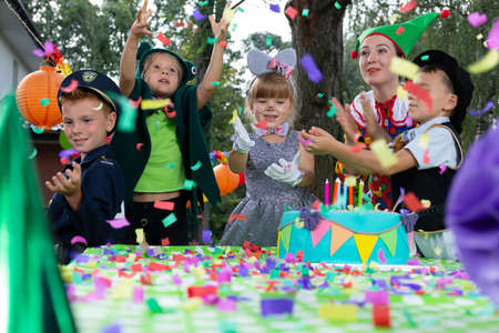 Smiling kids wearing in carnival costumes during colorful birthday party with cake