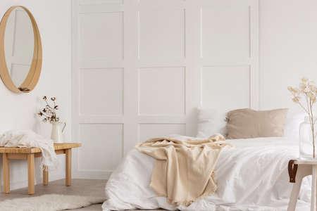 Weißes schlichtes Schlafzimmerdesign mit Spiegel, Kommode und bequemem Bett mit weißen Laken, echtes Foto