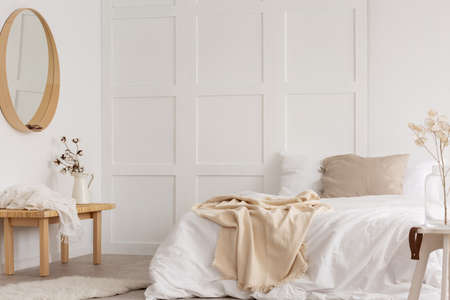 White simple bedroom design with mirror, dresser and comfortable bed with white sheets, real photo