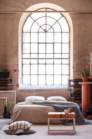 Pillows next to wooden table in front of bed with blanket in wabi sabi bedroom interior with window. Real photo
